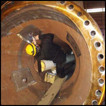 A technician working inside a pipeline section, attaching gauges.